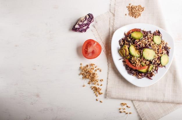 Salade végétarienne de chou mauve, de blé germé, de tomates et d'avocat sur une nappe en lin, vue de dessus.