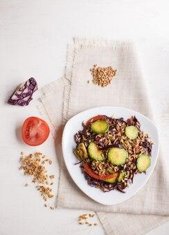 Salade végétarienne de chou mauve, de blé germé, de tomates et d'avocat sur une nappe en lin