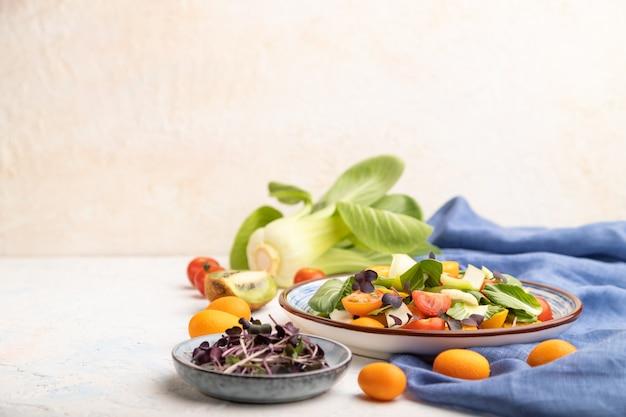 Salade végétarienne de chou pac choi, kiwi, tomates, kumquat, pousses microgreen sur fond de béton blanc et textile en lin bleu.