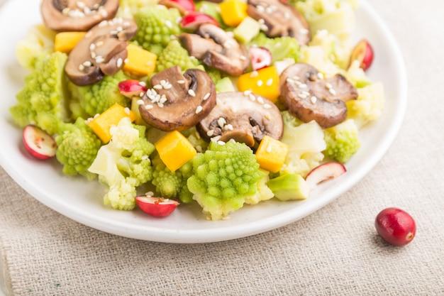 Salade végétarienne de chou romanesco, champignons, canneberge, avocat et citrouille sur un fond en bois blanc. vue latérale, mise au point sélective