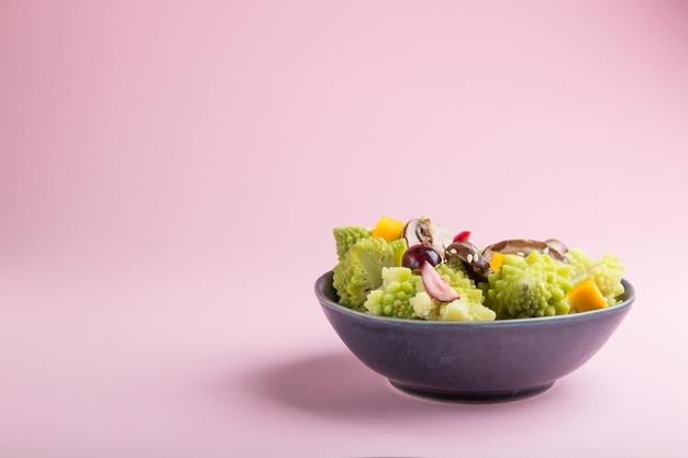 Salade végétarienne de chou romanesco, champignons, canneberge, avocat et citrouille sur fond rose pastel. vue latérale, espace copie.