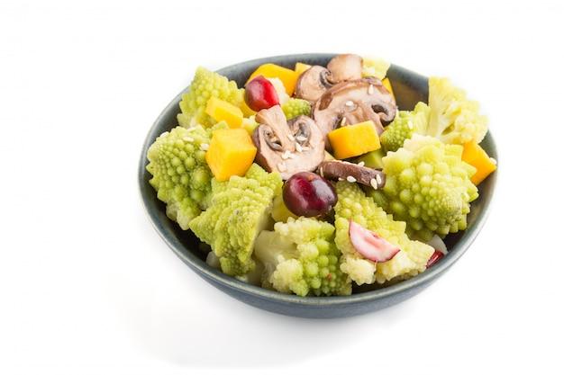 Salade végétarienne de chou romanesco, champignons, canneberge, avocat et citrouille isolé sur une surface blanche. vue de côté.