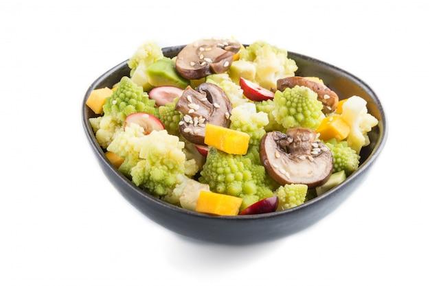 Salade végétarienne de chou romanesco, champignons, canneberge, avocat et citrouille isolés. vue de côté.