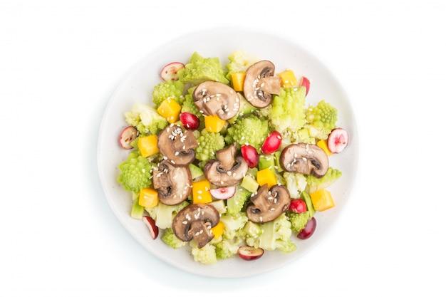 Salade végétarienne de chou romanesco, champignons, canneberge, avocat et citrouille isolés. vue de dessus.