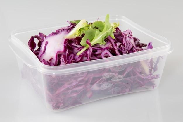 Salade végétarienne de chou rouge avec pomme verte râpée, huile et vinaigre dans un bol à emporter en plastique