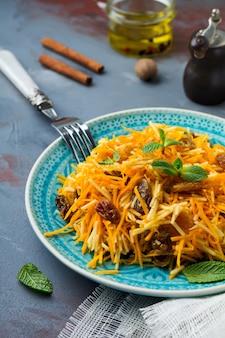 Salade végétarienne à la citrouille, pommes et raisins secs sur une surface sombre