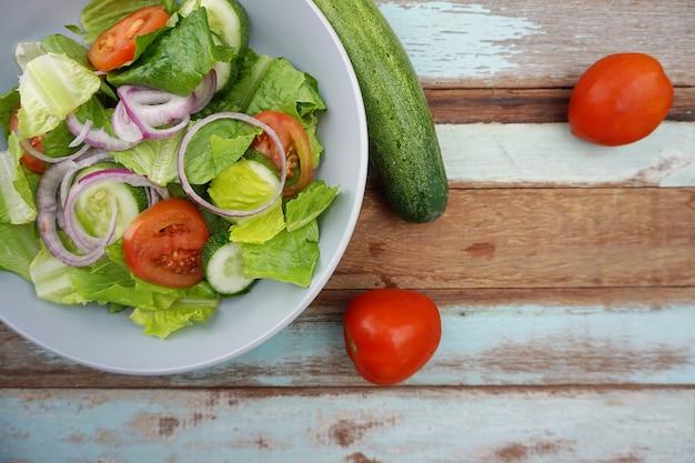 Salade végétarienne dans le bol bleu sur la plaque de bois de couleur