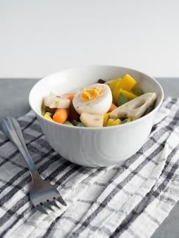 Salade végétarienne dans un bol avec une fourchette sur la table