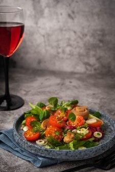 Salade végétarienne de feuilles, tomates, champignon mariné et verre de vin rouge sur fond gris, copy space