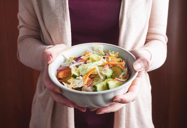 Salade végétarienne de légumes frais crus dans une assiette à la main de la femme. concept alimentation saine