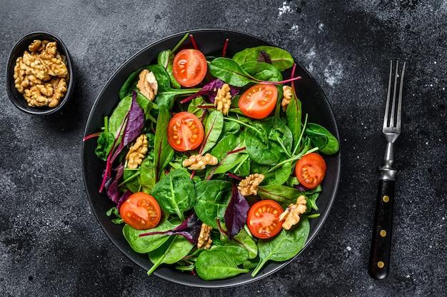 Salade végétarienne avec mélange de feuilles de mangold, de blettes, d'épinards, de roquette et de noix dans un saladier. fond noir. vue de dessus.