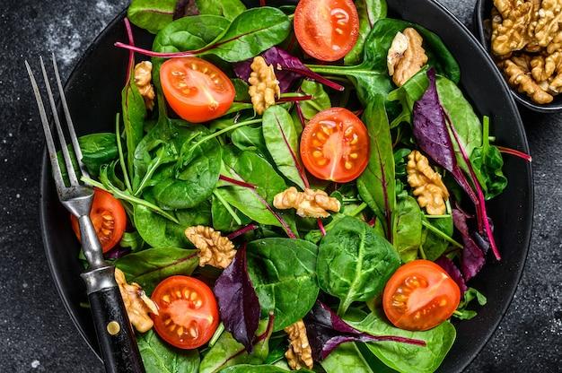 Salade végétarienne avec mélange de feuilles de mangold, de blettes, d'épinards, de roquette et de noix dans un saladier