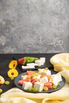 Salade végétarienne avec pastèque, fromage feta et raisins sur plaque en céramique bleue sur fond de béton noir et textile en lin jaune. vue latérale, espace copie, mise au point sélective.