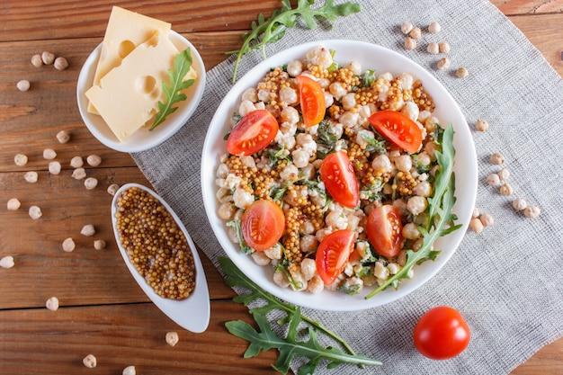 Salade végétarienne de pois chiches bouillis, fromage, roquette, moutarde et tomates cerises sur fond en bois marron.