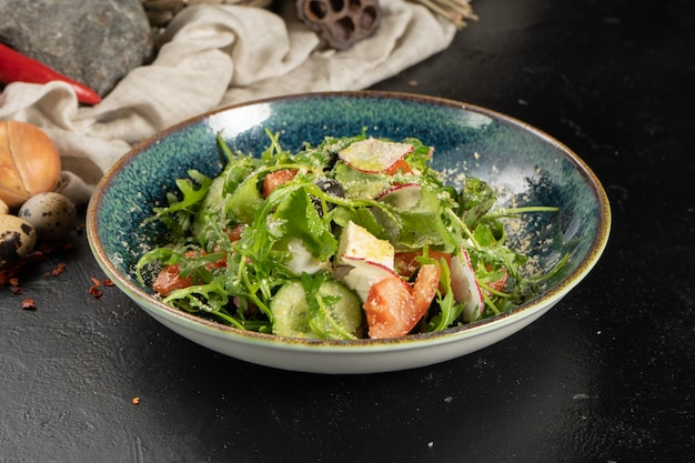 Salade végétarienne avec radis, roquette, tomates, concombre, œuf et parmesan.