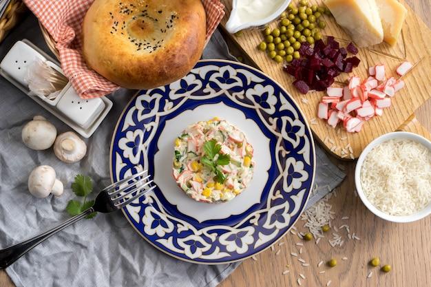 Salade végétarienne avec riz, concombre, maïs et bâtonnets de crabe dans une assiette avec un traditionnel ouzbek