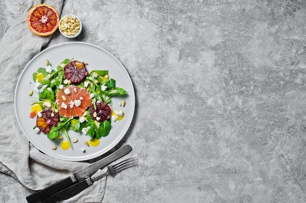 Salade végétarienne à la roquette, au pamplemousse, aux oranges rouges, aux noix et au tofu.