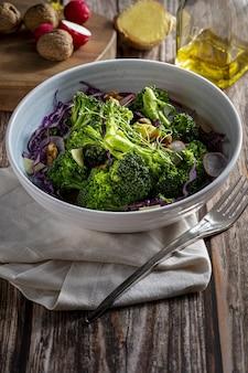 Salade végétarienne saine de brocoli cuit à la vapeur, radis frais, noix, chou rouge