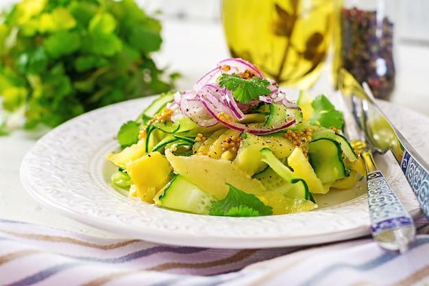 Salade végétarienne saine mangue, concombre, coriandre et oignon rouge à la sauce aigre-douce. nourriture thaï. repas sain.