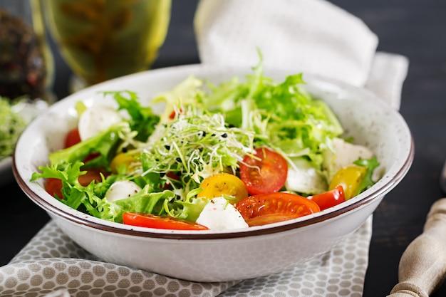 Salade végétarienne avec tomate cerise, mozzarella et laitue.