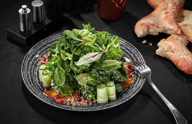 Salade de verdures vinaigrette concombre kaki noix et grenade