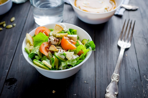 Salade vert clair frais avec concombre, laitue, avocat, tomates, sur une table en bois sombre. concept de mode de vie alimentaire sain.
