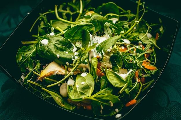 Salade verte au basilic et sauce à la crème à l'ail blanc pour une alimentation saine, service de livraison de nourriture et concept de commande en ligne