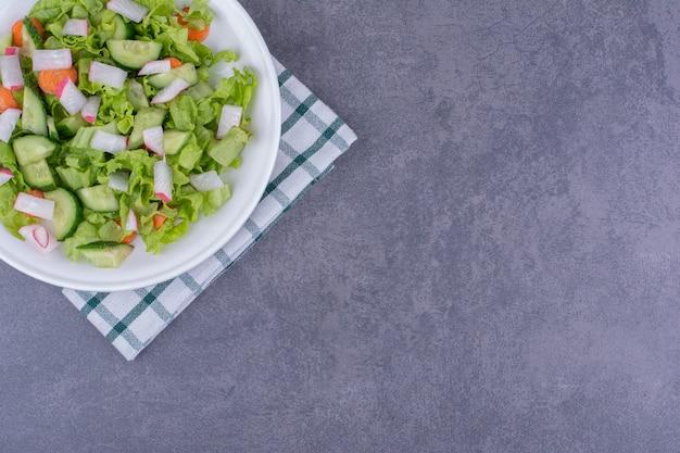 Salade verte aux herbes et épices dans une assiette en céramique