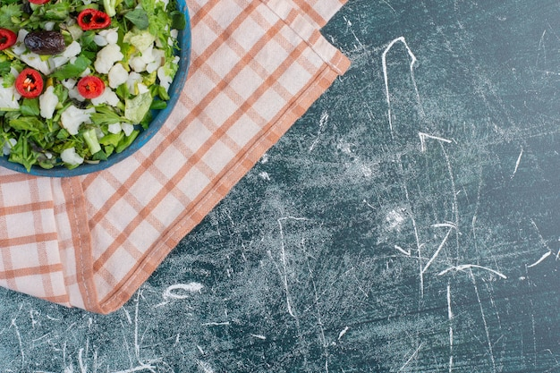 Salade verte aux herbes et ingrédients hachés.