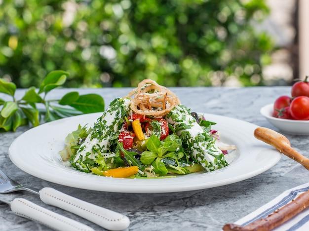 Salade verte aux herbes et à la tomate.
