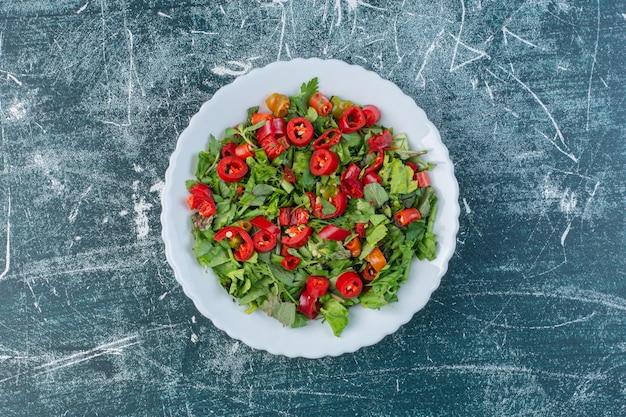Salade verte aux piments rouges hachés.