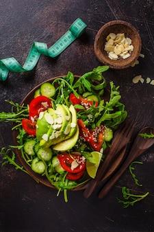 Salade verte à l'avocat, tomates, concombres et noix dans une assiette en bois, centimètre sur noir