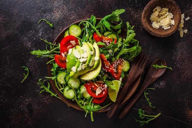 Salade verte à l'avocat, tomates, concombres et noix dans une assiette en bois sombre
