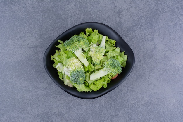 Salade verte dans une assiette sur une surface bleue