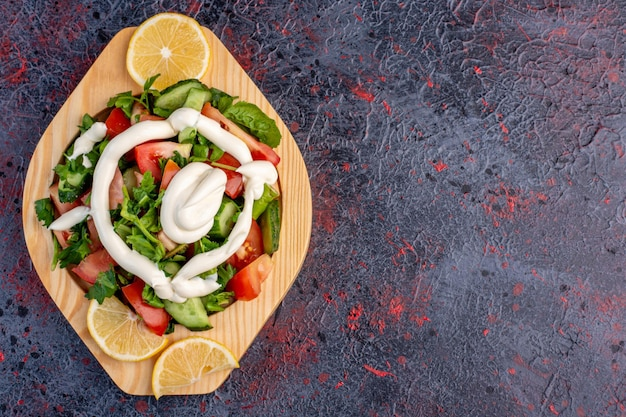 Salade verte dans un plat en bois avec sauce mayonnaise.
