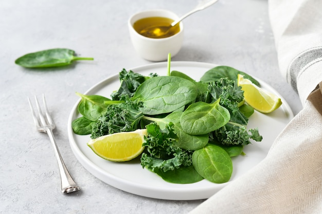 Salade verte d'épinards biologiques et feuilles de chou frisé avec jus de citron et huile d'olive.