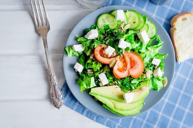 Salade verte fraîche avec concombre, laitue, avocat, tomates et fromage à pâte molle