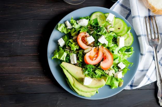 Salade verte fraîche avec concombre, laitue, avocat et tomates et verre d'eau sur la table.