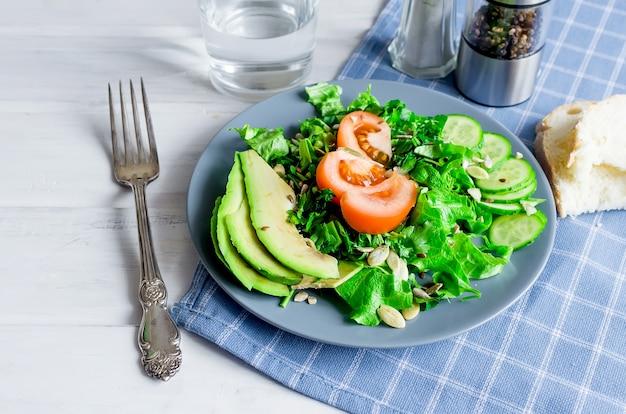 Salade verte fraîche avec concombre, laitue, avocat et tomates et verre d'eau