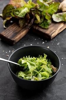 Salade verte fraîche dans un bol sombre