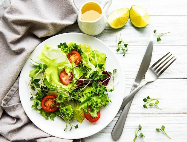 Salade verte fraîche avec des tomates et des microgreens sur bois blanc