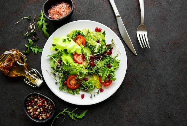 Salade verte fraîche avec des tomates et des microgreens sur une surface de béton noir