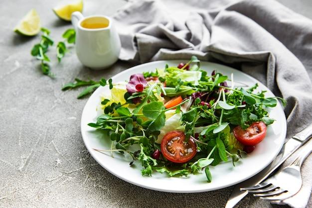Salade verte fraîche avec des tomates et des microgreens sur une surface en béton