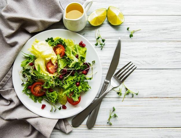 Salade verte fraîche avec des tomates et des microgreens sur une surface en bois blanche