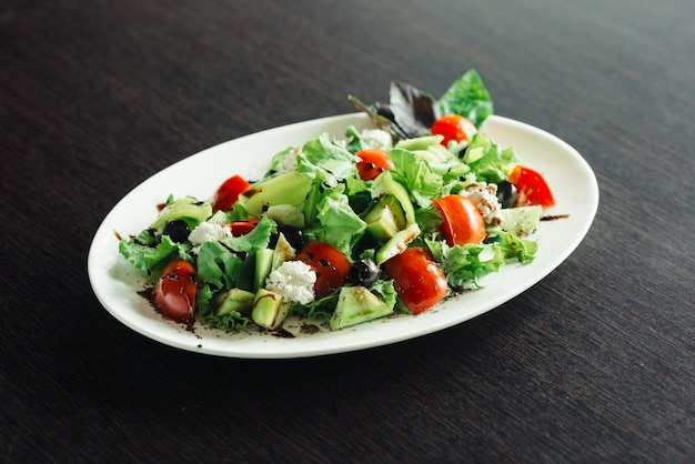 Salade verte et fromage sur une assiette blanche