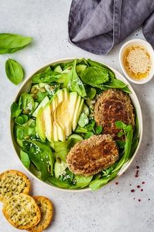 Salade verte avec des galettes d'avocat, de concombre et de lentilles dans une assiette blanche.