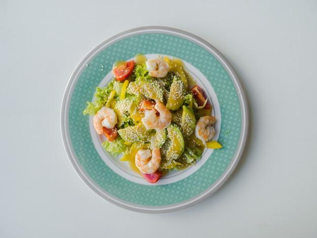 Salade verte légère aux crevettes et avocat sur une assiette.