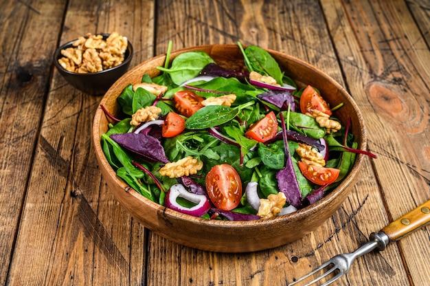 Salade verte de légumes frais avec feuilles de mangold, blettes, épinards, roquette et noix. fond en bois. vue de dessus.