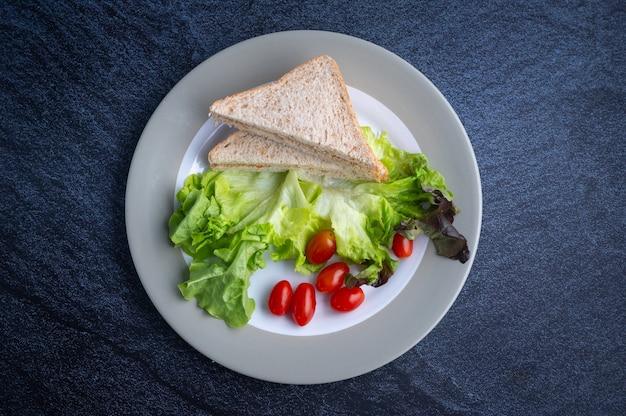 Salade verte avec tomates et pain tranché, repas végétalien du matin, légumes, à base de plantes, plat d'accompagnement, concept de style alimentaire, nourriture saine, vue de dessus, fond sombre.