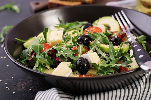 Salade verte avec tranches d'avocat, tomates cerises, olives noires et fromage